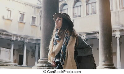 Beautiful female tourist with camera walking and looking at...