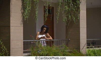Beautiful female traveler standing on balcony of her villa and using her smartphone. Young brunette enjoying her travelling and waiting for friends on terrace of their house to explore surroundings.