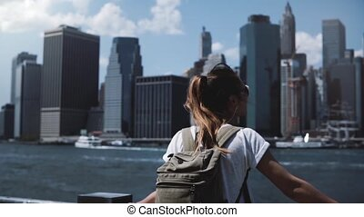 Beautiful female traveler with backpack raises arms wide open with excitement near Manhattan city skyline in New York.