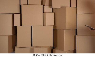 Beautiful female warehouse worker in orange uniform walking against brown cardboard boxes backround. 4K video