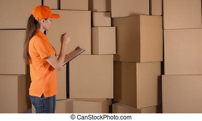 Beautiful female warehouse worker in orange uniform counting items and making records against brown cartons backround. 4K studio lighting video