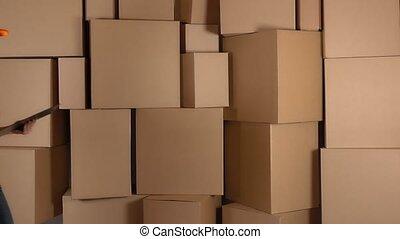 Beautiful female warehouse worker in orange uniform searching item against brown cardboard boxes backround. 4K video