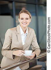 beautiful female white collar worker having coffee break at...