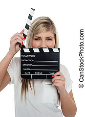 Beautiful female with clapperboard. It's showtime.
