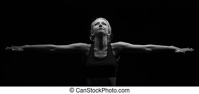 Beautiful fit and healthy blond woman in black top in dark with arms stretched artistic conversion