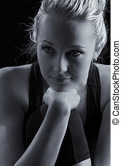 Beautiful fit and healthy blond woman portrait in black top with knee drawn up artistic conversion