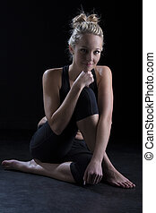 Beautiful fit and healthy blond woman portrait in black top crouch on floor