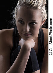 Beautiful fit and healthy blond woman portrait in black top with knee drawn up