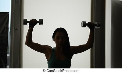 beautiful fit girl doing exercises with dumbbells