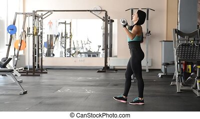 beautiful fit girl doing exercises with dumbbells in the gym