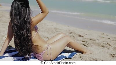 Beautiful fit girl in bikini sitting on sand