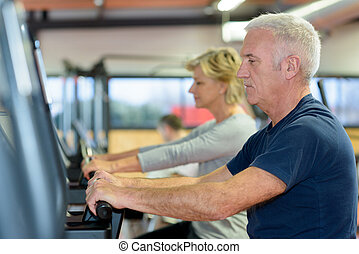 beautiful fit senior couple in gym doing cardio work out