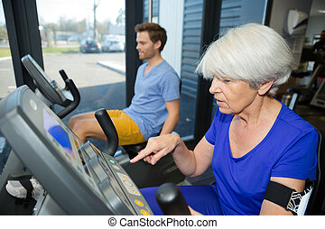 beautiful fit senior woman in gym doing cardio work out