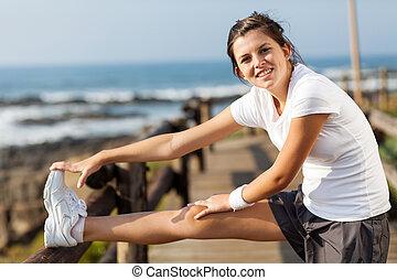 fit teen girl exercising at beach
