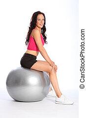 Beautiful fit woman balancing on fitness ball
