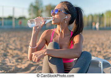 Beautiful fitness athlete woman drinking water after work...