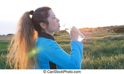 Beautiful fitness athlete woman drinking water after work ...