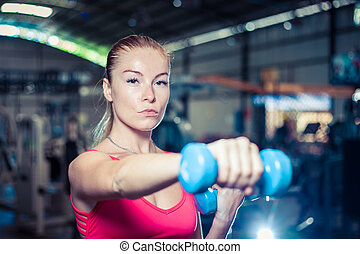 Beautiful fitness girl with dumbbells. Attractive woman in gym.