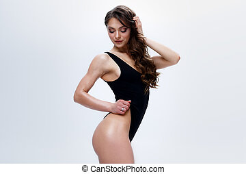 Beautiful fitness girl with long hair and sexy body is posing on a white background in a black bodysuit