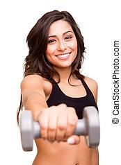 Beautiful fitness woman lifting weights