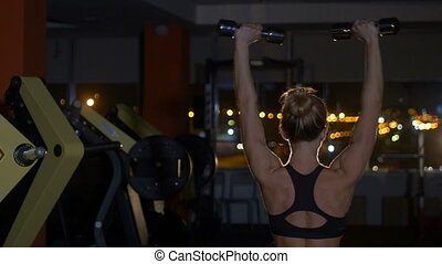 Beautiful fitness woman with lifting dumbbells