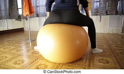 Beautiful fitness woman with toned body sitting on the fitness ball and doing exercises. slow motion