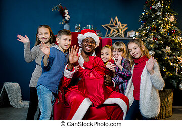 Beautiful five children, three girls and two boys, laughing, hugging African Santa Claus, waving their hands. Christmas holidays, New Year