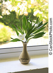 Beautiful floral arrangement in a vase on the window.