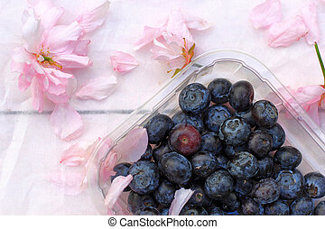 Beautiful floral background with Spring flowers and a box of blueberries