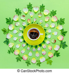 Beautiful floral pattern of pink rose petals and yellow cup of hot aromatic coffee on paper green background.
