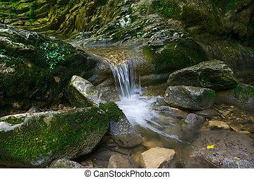 Beautiful flow of water flowing between stones