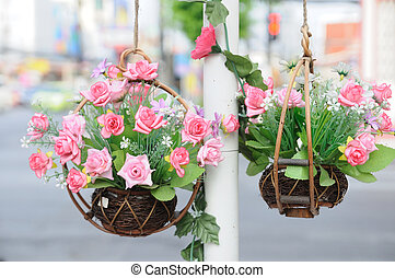 Beautiful flowers in basket hanging aside street.