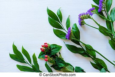 Beautiful flowers of lavender and red berries on white wooden background