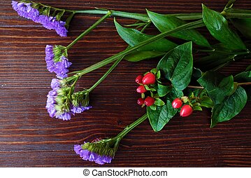 Beautiful flowers of lavender and red berries on wooden background