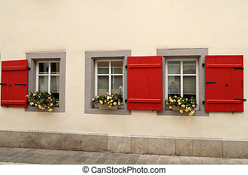 Beautiful flowers on the windows with shutters