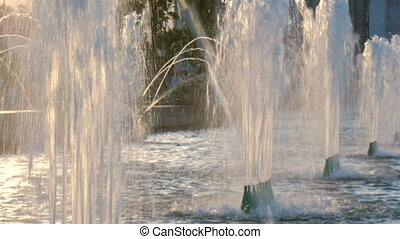 Beautiful fountain in the city park. The sun illuminates the splashes of water. Shining splash of water. Close up