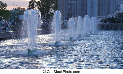 Beautiful fountain in the city park. The sun illuminates the splashes of water. Shining splash of water.