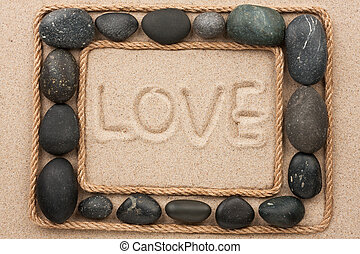 Beautiful frame of rope and stones on the sand with text love