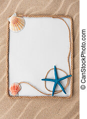Beautiful frame of rope, stars and seashells with a white background on the sand, with place for your image, text.