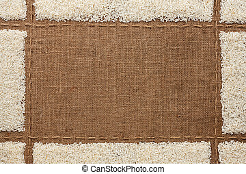 Beautiful frame with rice on sackcloth