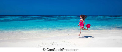 Beautiful free young woman jumping on the exotic sea