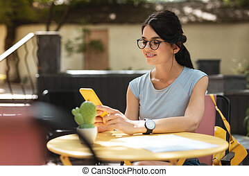 Beautiful freelancer wearing glasses sitting in cafe waiting for her partner