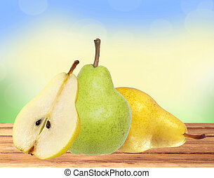 Beautiful fresh green and yellow pears on wooden table over nature background