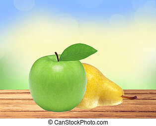 Beautiful fresh green apple and yellow pear on wooden table over nature background