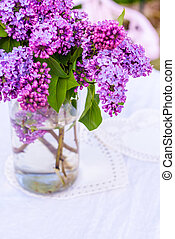 Beautiful, fresh lilac flowers in a glass vase, still life composition