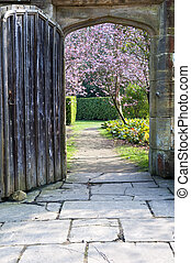 Beautiful fresh Spring blossom trees seen through old wooden door and stone archway