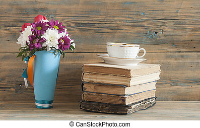 Beautiful fresh spring flowers with stack of books on a table