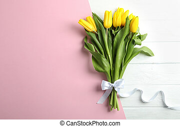 Beautiful fresh yellow tulips on color background, top view. Space for text