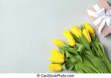 Beautiful fresh yellow tulips on gray background, top view. Space for text