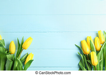 Beautiful fresh yellow tulips on wooden background, top view